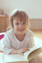 Portrait of smiling little girl with book - LVF001345