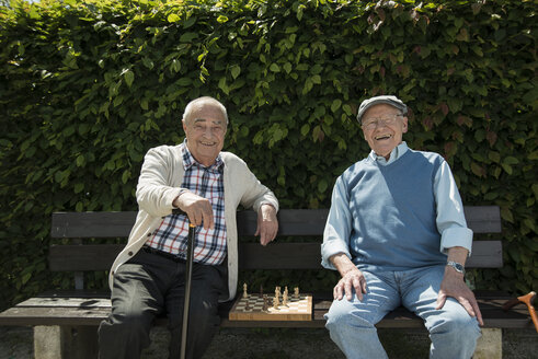 Two old friends sitting on park bench with chess - UUF000739
