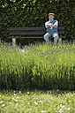 Happy old man sitting on park bench with lavender field in the foreground - UUF000679