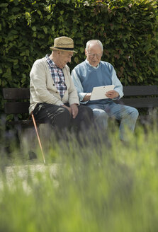 Two old men using tablet computer in the park - UUF000698