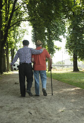 Two old friends walking in the park with football, back view - UUF000714