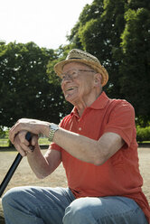 Portrait of happy old man sitting on park bench with walking stick - UUF000722