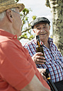 Two old friends toasting with beer bottles in the park - UUF000726