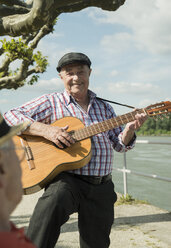 Germany, Rhineland-Palatinate, Worms, portrait of old man with guitar at promenade of Rhine River - UUF000730