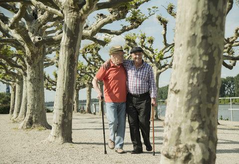 Germany, Rhineland-Palatinate, Worms, two old men walking arm in arm at promenade of Rhine River - UUF000732
