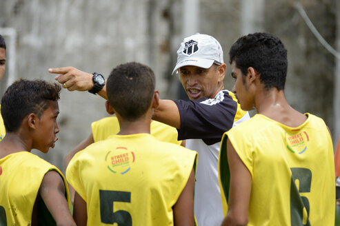 Brazil, Fortaleza, Coach talking to street children on soccer ground - FLK000290