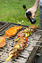 Man holding beer bottle at barbecue grill with meat - ON000595