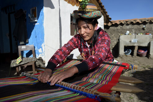 Peru, Quispillacts, Young woman weaving traditional cloth - FLK000244