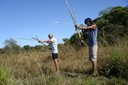 Brazil, Mato Grosso, Sangradouro, Xavante men hunting with bow and arrow - FLK000261