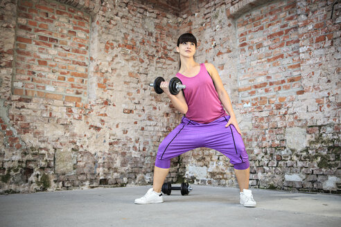 Woman with barbells doing fitness exercise in a gym - VTF000268