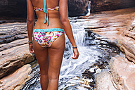 Australia, Western Australia, Karijini National Park, Hancock Gorge, woman in bikini standing at stream, partial view - MBEF001020