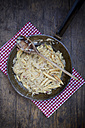 Frying pan of finger-shaped potato dumplings with sauerkraut and bacon on cloth - LVF001369
