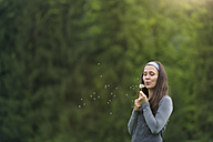 Young woman blowing blowball in front of green background - MW000048