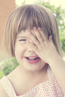 Portrait of laughing little girl covering one eye with her hand - LVF001354