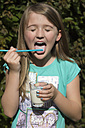 Portrait of girl licking milk from drinking straw - YFF000160