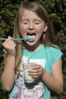 Portrait of girl licking milk from drinking straw - YFF000160
