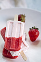 Three strawberry yogurt popsicles and strawberries on a plate, close-up - SBDF000979