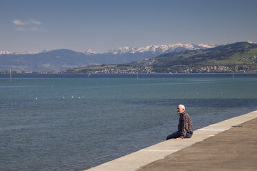 Switzerland, Thurgau, Arbon, One senior man sitting at lakeside promenade - WIF000747