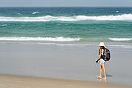 Australia, New South Wales, Pottsville, girl with backpack walking on beach - SHF001372