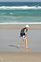 Australia, New South Wales, Pottsville, girl with backpack walking on beach - SHF001374