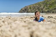 Australia, New South Wales, Byron Bay, Broken Head nature reserve, girl playing in sand on beach - SHF001375