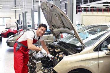 Car mechanic in a workshop working at car - LYF000042