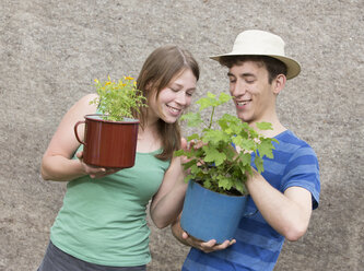 Young couple with two potted plants, Tagetes tenuifolia and Ribes - DISF000838