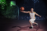 Basketball player on a street basketball court at night - VTF000275