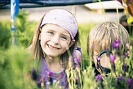 Brother and sister watching flowers with magnifying glass - SARF000671