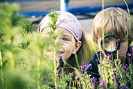 Brother and sister watching flowers with magnifying glass - SARF000672