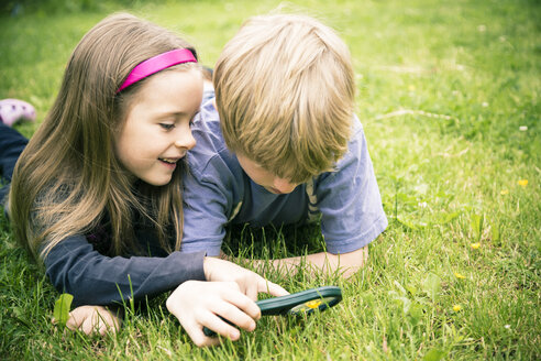 Brother and sister lying on meadow watching flowers with magnifying glass - SARF000675