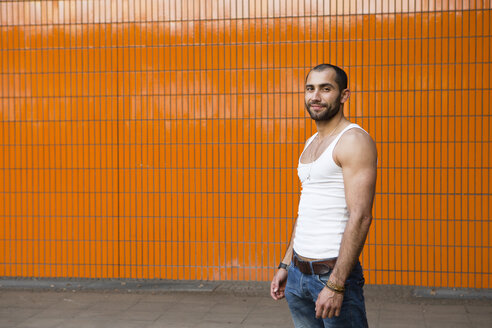 Portrait of smiling young man in front of orange tiled wall - FX000011