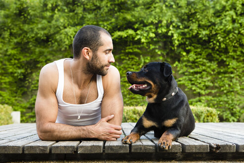 Portrait of young man face to face with his Rottweiler lying on boardwalk - FX000016