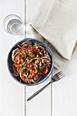 Bowl of spelt pasta with tomatoes and basil, glass of water, napkin and fork on white wood - EVGF000628
