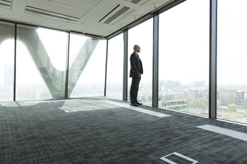 Businessman on empty office floor looking out of window - WESTF019467