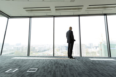 Businessman on empty office floor looking out of window - WESTF019472
