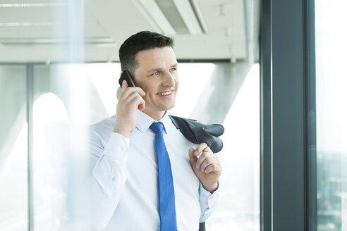 Businessman in office on cell phone - WESTF019271