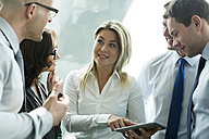 Businesspeople in office with woman using digital tablet - WESTF019308