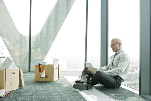 Businessman using laptop on empty office floor with cardboard box - WESTF019316