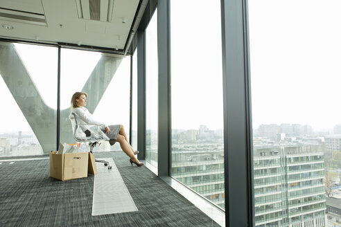 Businesswomanp on empty office floor with cardboard box looking out of window - WESTF019491