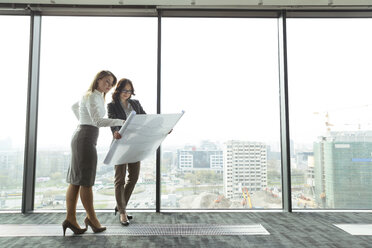 Two businesswomen in office looking at blueprint - WESTF019498
