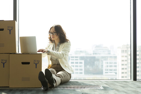 Businesswoman using laptop on empty office floor with cardboard boxes - WESTF019500