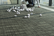 Businessman sitting on office floor surrounded by crumpled paper - WESTF019299