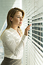 Businesswoman looking through blinds - WESTF019333