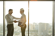 Two businessmen in sunny office shaking hands - WESTF019389