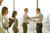 Two businessmen in sunny office shaking hands - WESTF019525