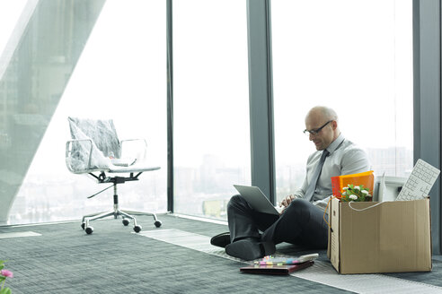 Businessman using laptop on empty office floor with cardboard box - WESTF019366