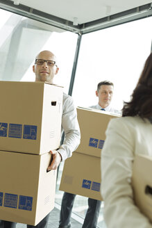 Businesspeople in office with cardboard boxes - WESTF019459