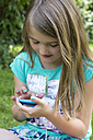 Little girl sitting with smartphone in the garden - YFF000164
