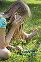 Little girl hearing music with smartphone in the garden - YFF000166